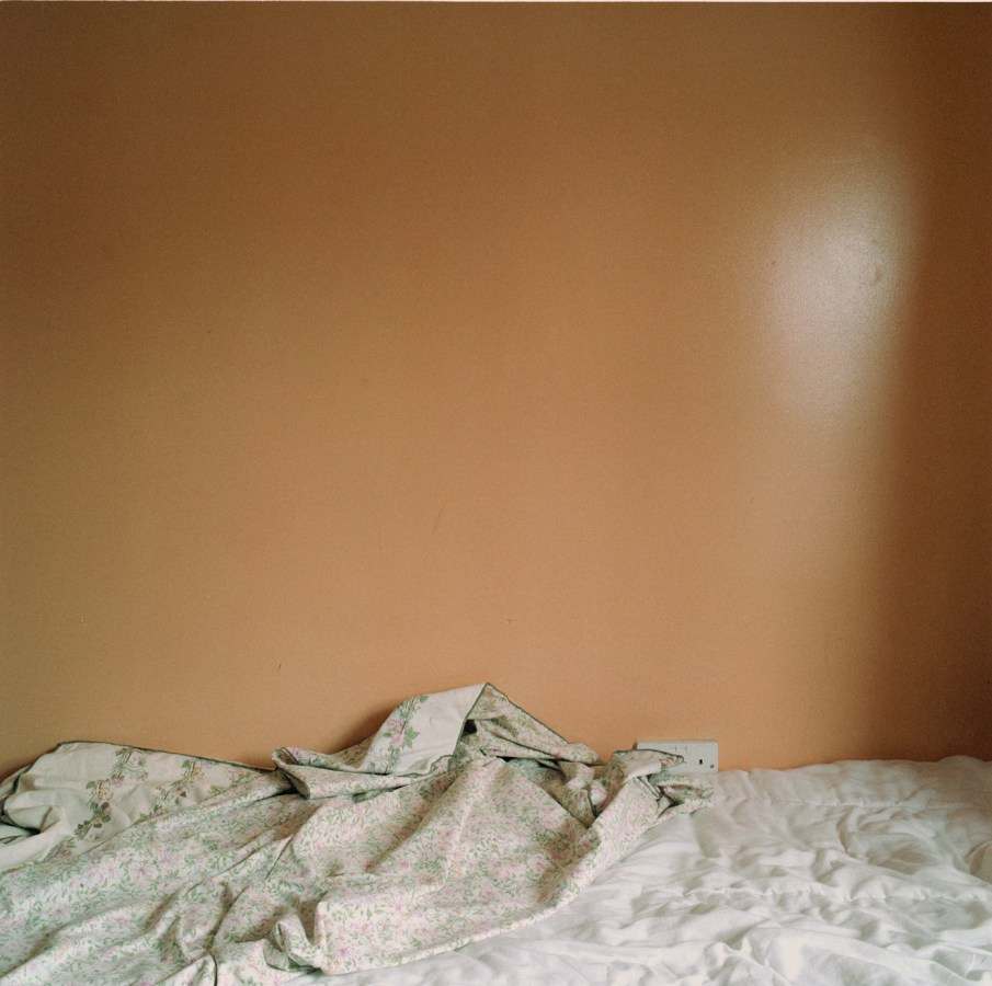 Color photograph of an umade bed in front of a burnt orange wall.