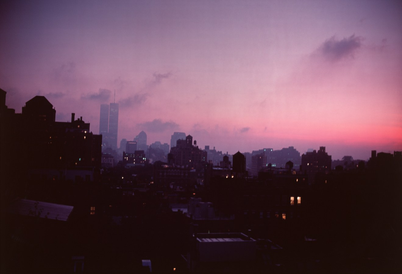 Color photograph of a city skyline at sunset under a pink and purple sky
