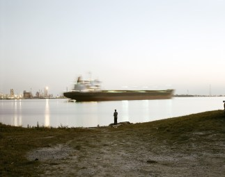 Color photograph of a person standing on a shore of an industrial waterway with a passing cargo ship and power plant on the horizon