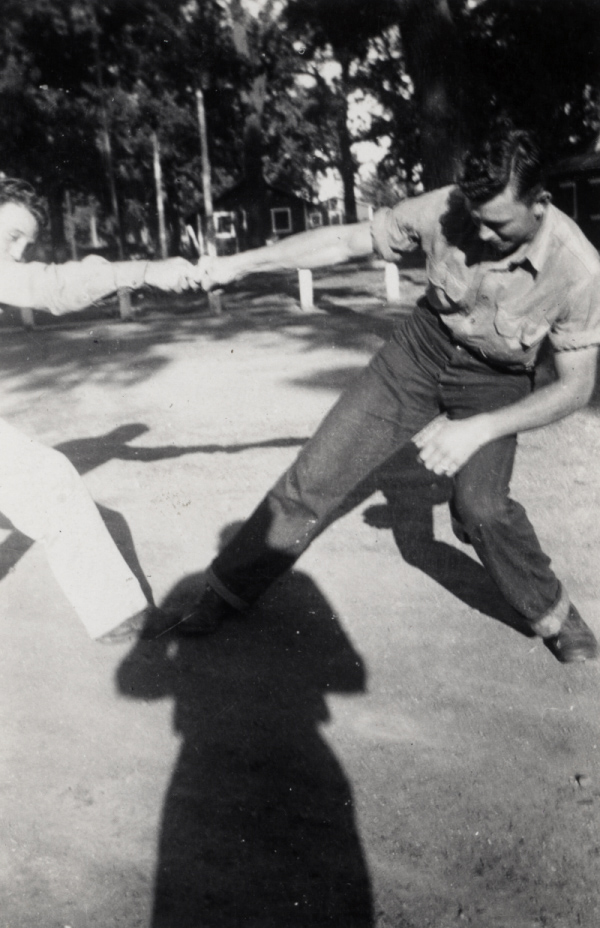 Black and white photograph of two people pulling on each other's arms with the photographer's silhouette on the ground