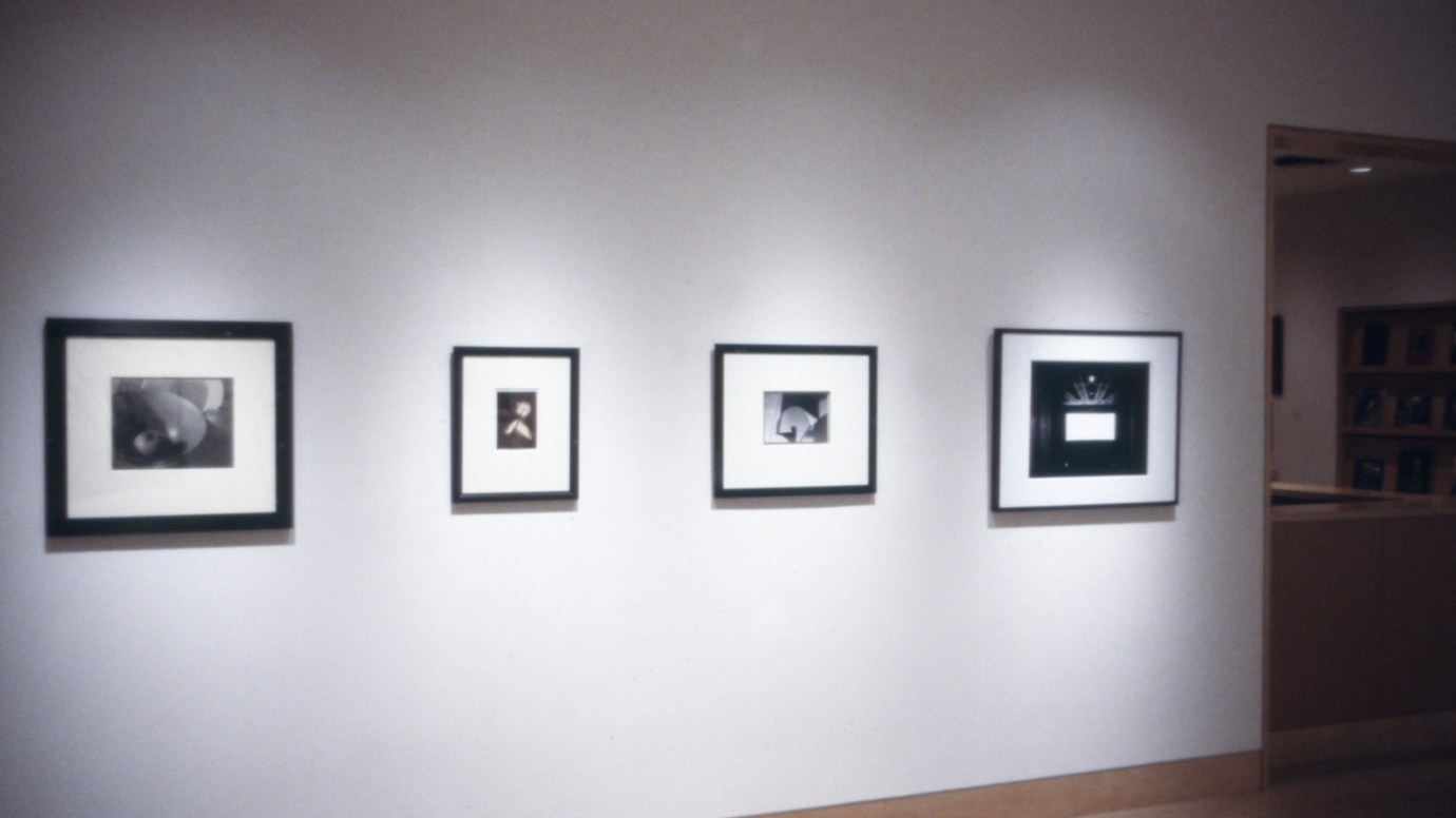 Installation photograph of four framed black and white prints on a gallery wall
