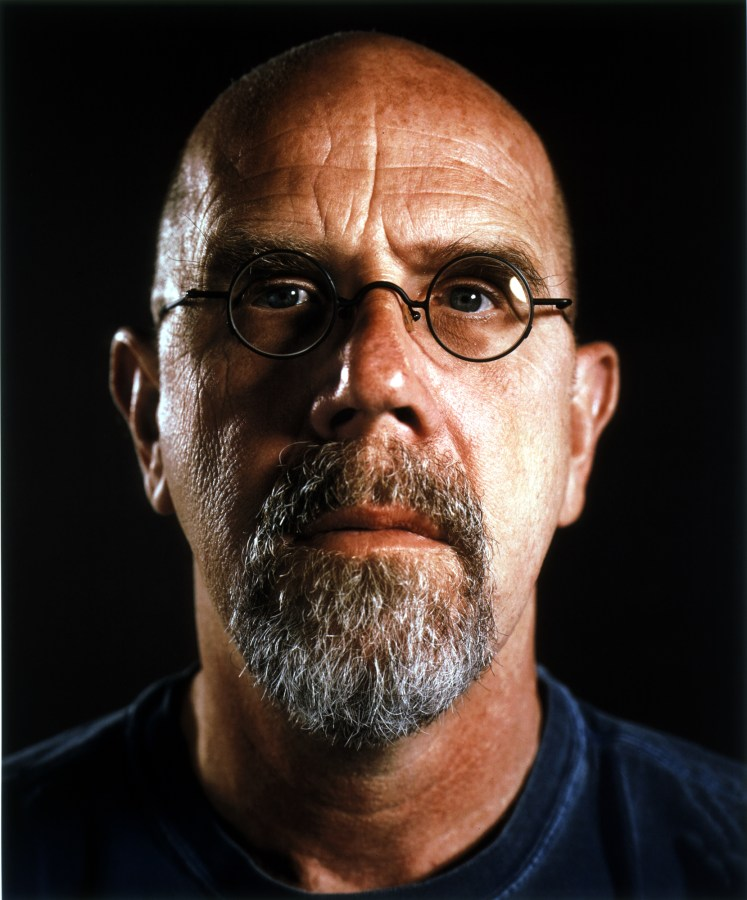 Color portrait photograph of a bald man with a greying beard and round glasses