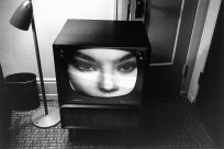 Black and white photograph of a television screen displaying a close up of a woman's eyes and nose