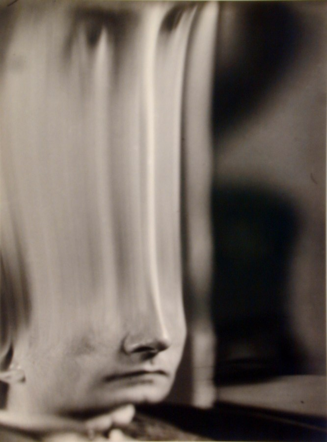 Black and white photograph of a distorted face stretched in the middle