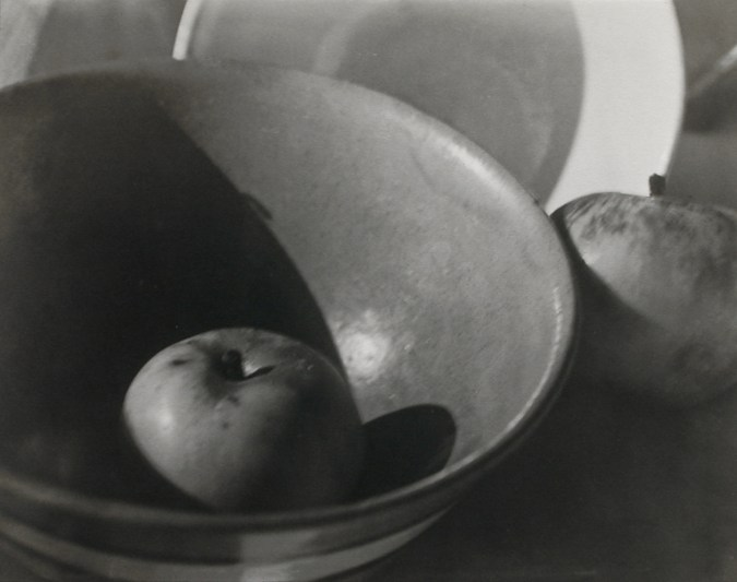 Black and white photograph of an apple in a bowl with another apple next to it