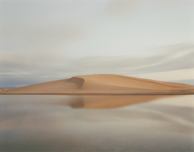 Color photograph of a sand dune over a flooded plane.