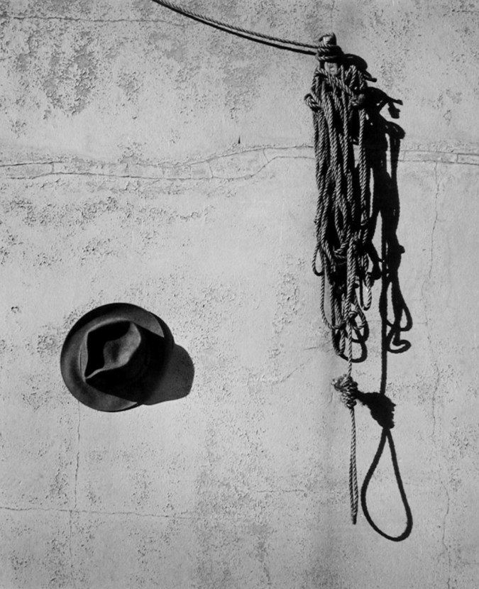Black and white photograph of a hat next to a tangle of hanging rope