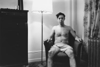 Black and white photograph of a man wearing only boxer shorts seated in an armchair in the corner of a living room