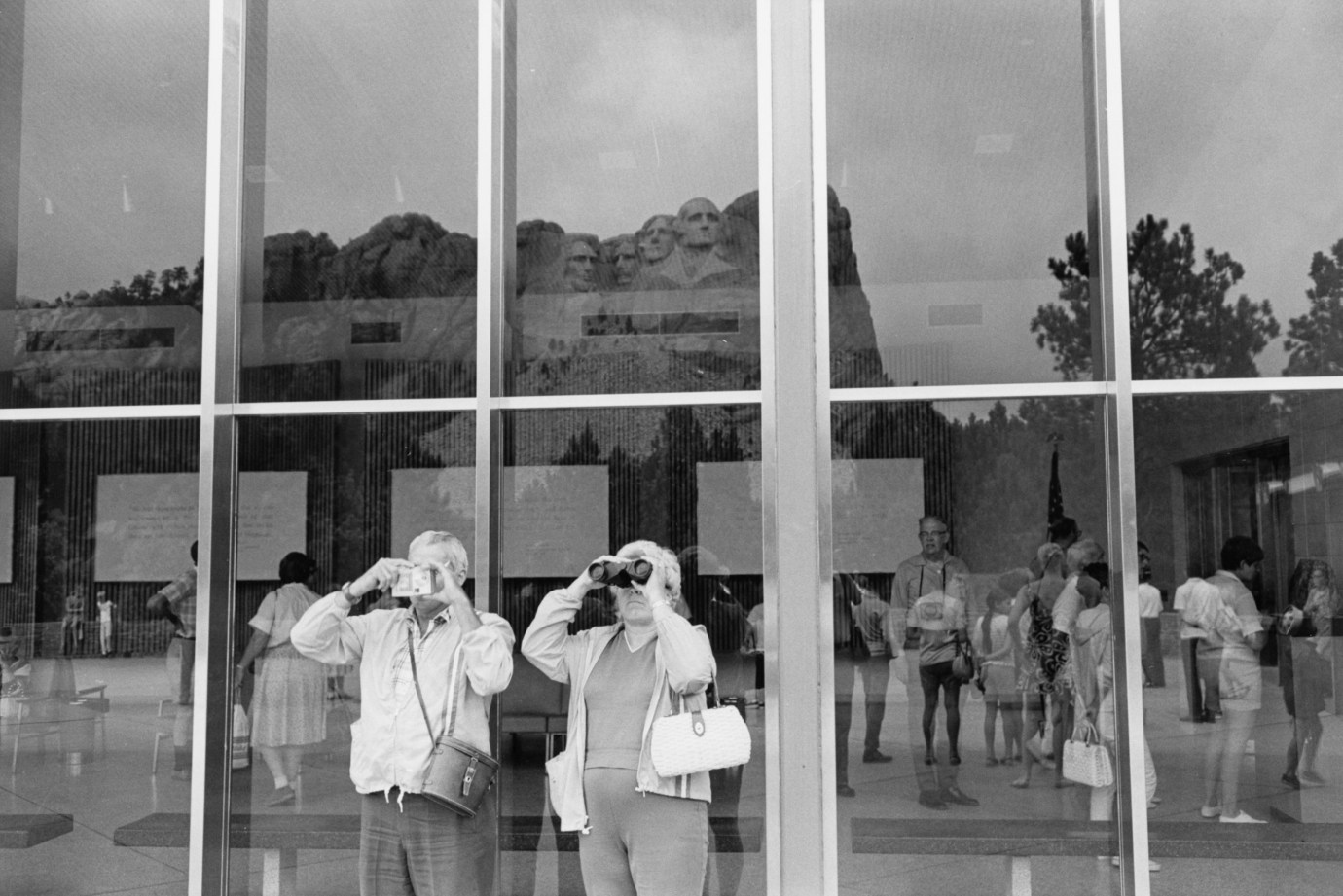 Black-and-white photograph of an elderly couple looking with binoculars towards the left. Mt. Rushmore is reflected in the windows behind them.