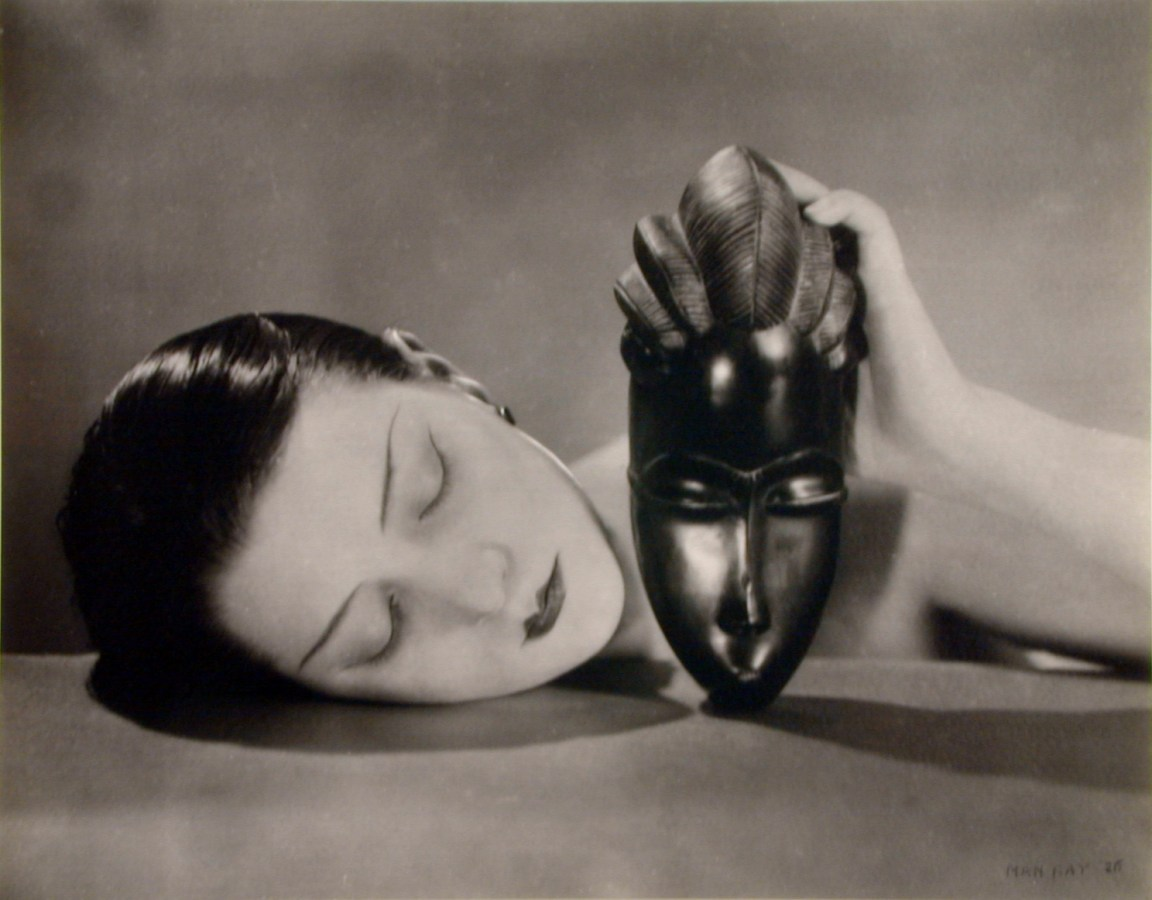 Black and white photograph of a woman laying her head on a table while propping up an African mask in one hand