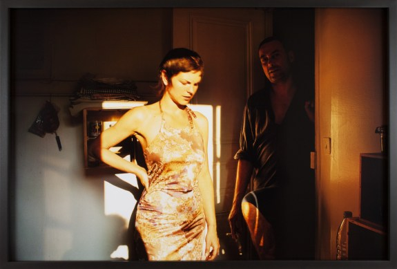 Color photograph of a young woman standing in sunlight from a window in front of a man in a shadowed doorway