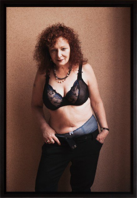 Color photograph of a woman in a lace bra and jeans with hands in her pockets standing in front of a beige wall