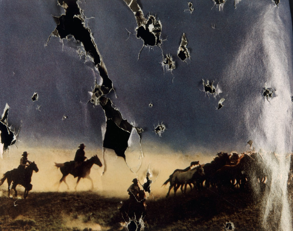 Color photograph of a photograph riddled with bullet holes of cowboys on horseback rounding up horses