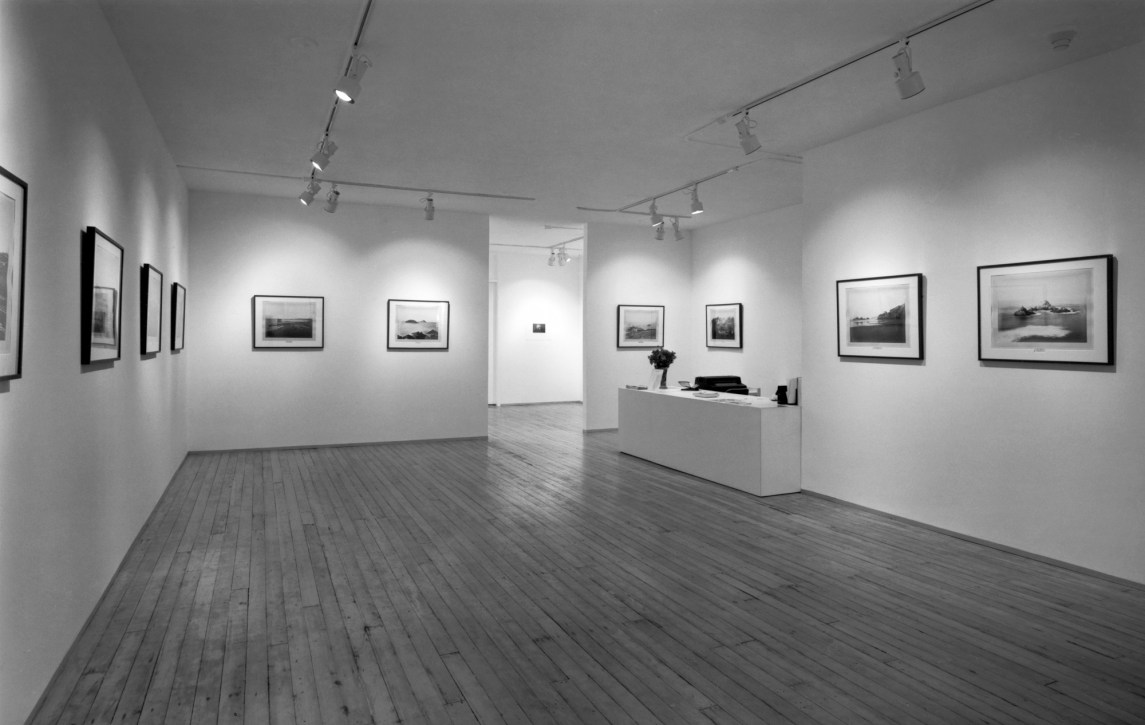 Black-and-white photograph of a gallery interior with works framed on the walls.