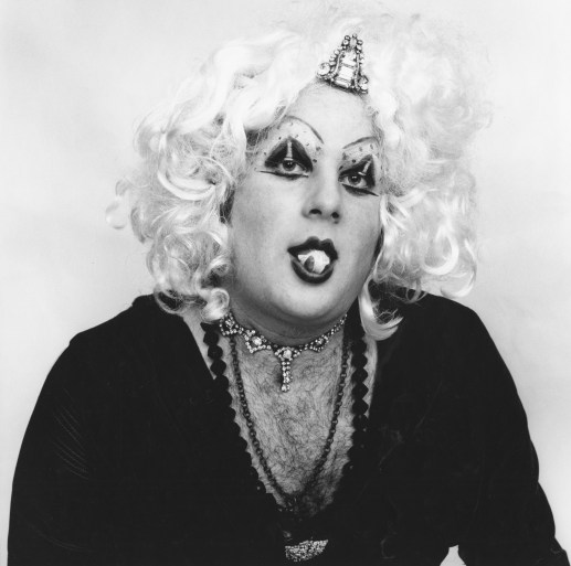 Black-and-white figure of a sitter wearing a blonde wig, heavy makeup, and a deep-cut shirt showing off a hairy chest, popping chewing gum