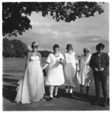Black and white photograph of five masked people standing in front of a wide lawn