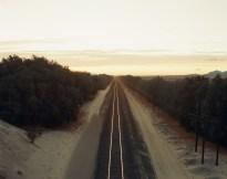 Color photograph of train tracks receding into the horizon.