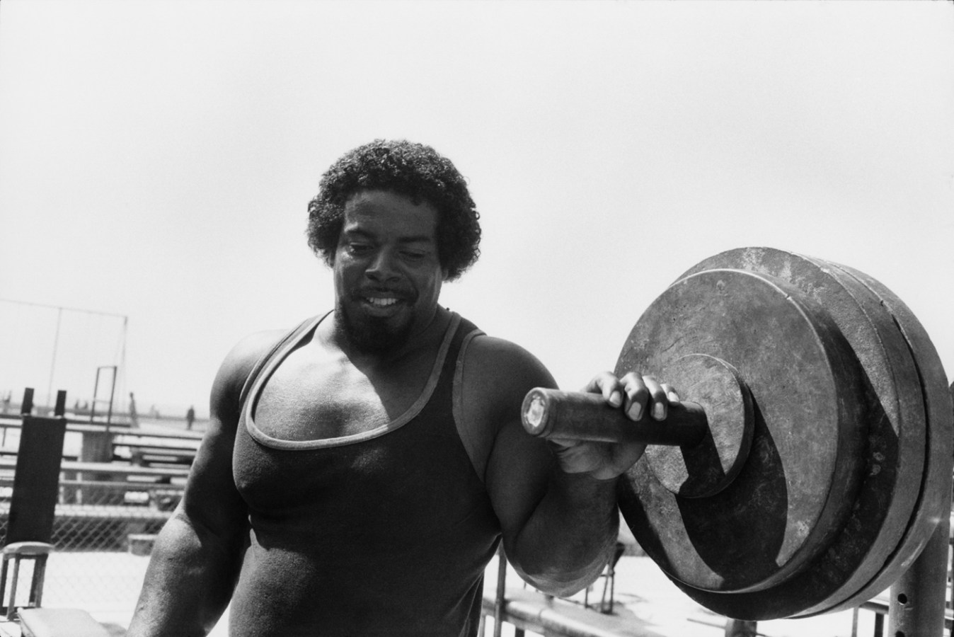 Black-and-white photograph of a muscular man in a tank top next to a large barbell weight