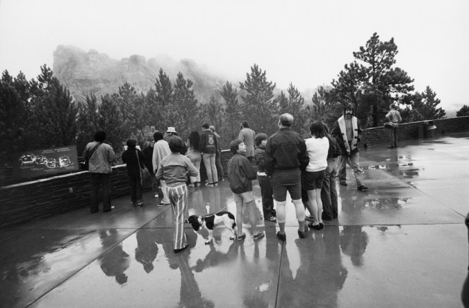 Black-and-white photograph of a family of tourists approaching a look out point of an overcast rock outcrop