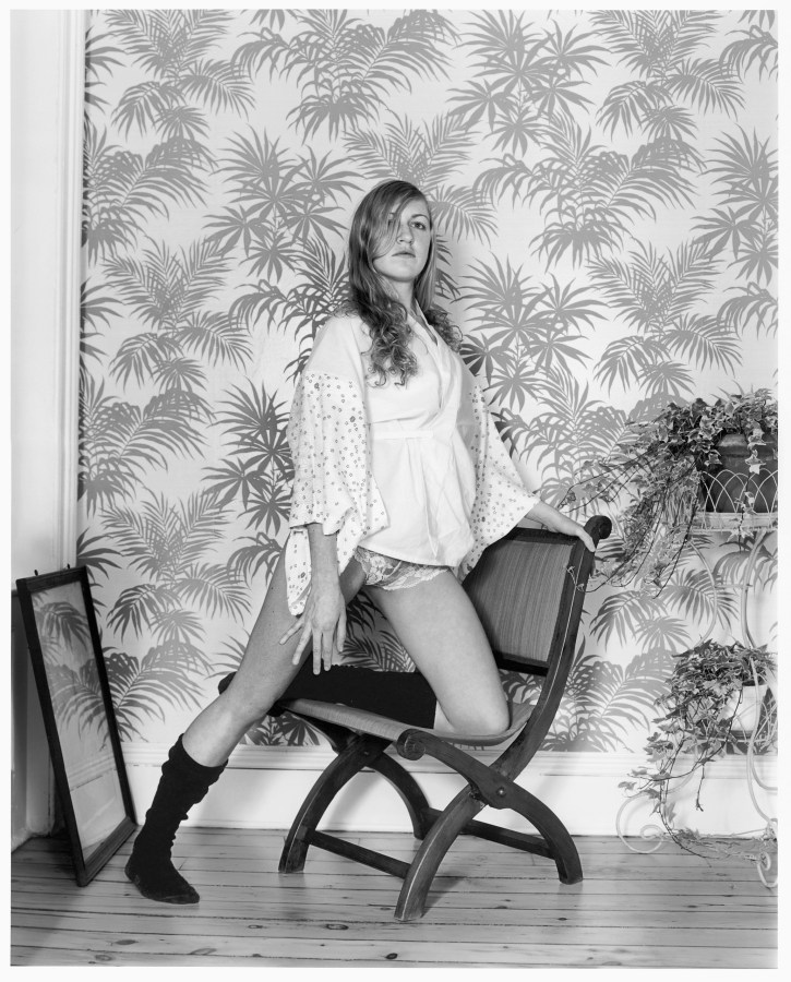 Black-and-white photograph of a woman resting one knee on a chair in front of a palm-leaf patterned wallpaper