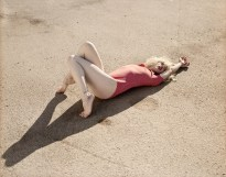 Color photograph of a woman in a red bodysuit lying down on asphalt