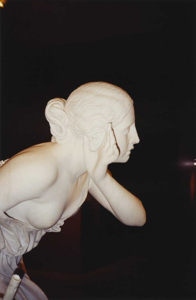 A color photograph of a marble sculpture of a woman in profile, with her hand to her ear.