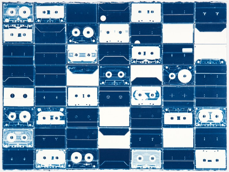 Horizontal image of a grid of white cassette tapes and their outlines on a background of deep blue