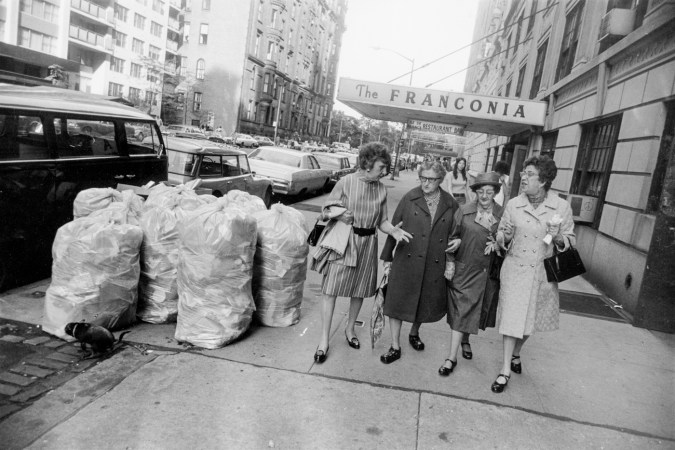 Black-and-white photograph of a group of older women conversing and walking past a pile of trash bags on the sidewalk