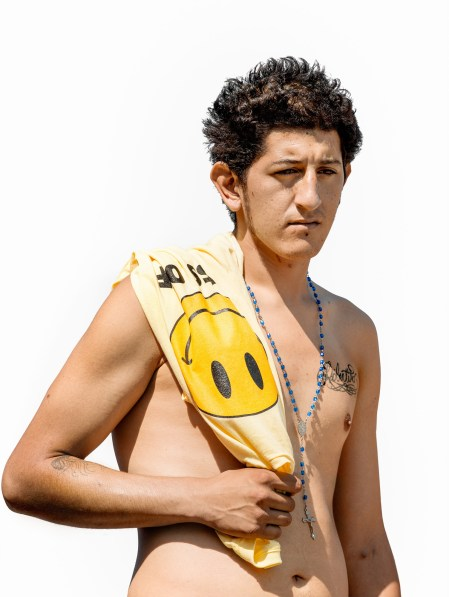 Color photographic portrait of a shirtless young man holding a t-shirt over his shoulder
