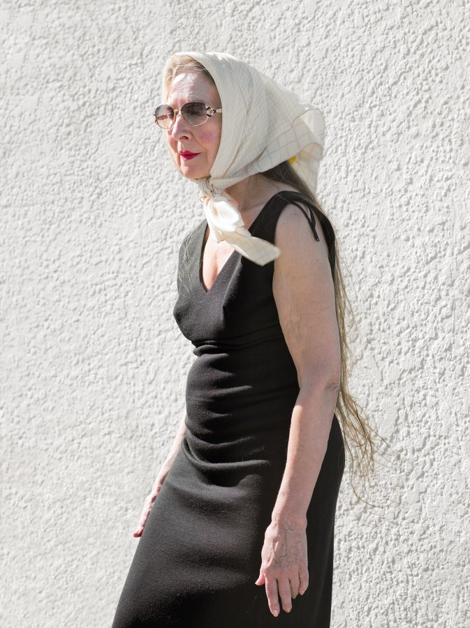 Color photograph of a woman in sunglasses and a scarf on her head standing in front of a blank white wall