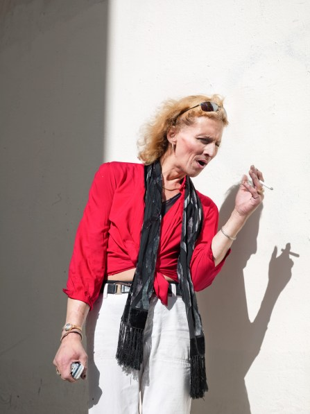 Color photograph of a woman in a tied red top and black scarf holding a cigarette
