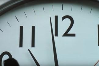 Video still of a clockface up close