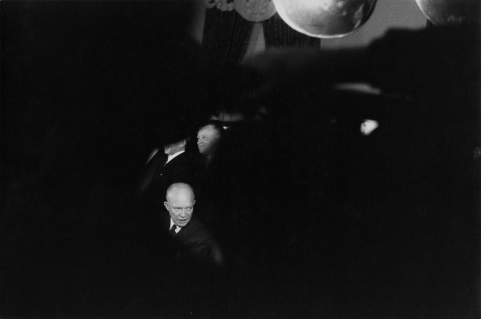 Black-and-white photograph of a man's face isolated amidst a blurred black foreground