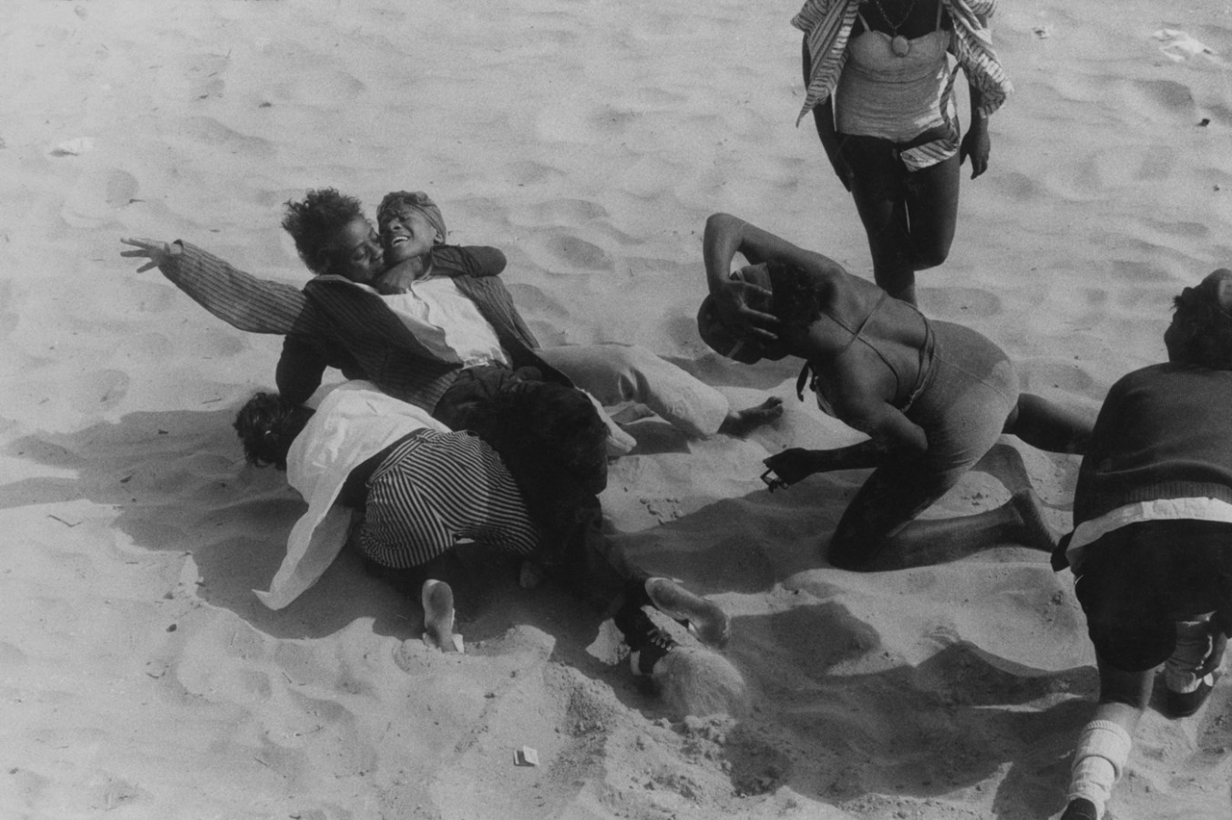 Black-and-white photograph of six people embracing and kneeling on the sand