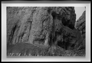 Black-and-white photograph of the stony base of a rough bare cliff face