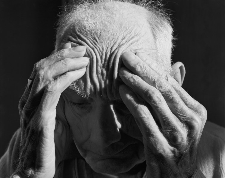 Close up black-and-white photograph of an elderly man rubbing his forehead with both hands