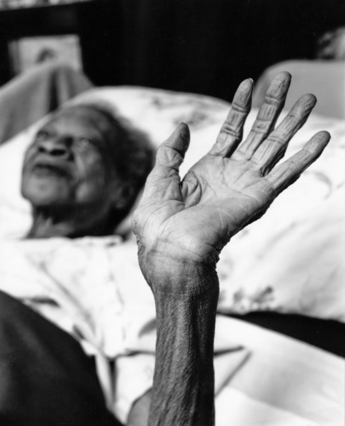 Black-and-white photograph of an elderly woman lying in bed raising her open hand to the viewew