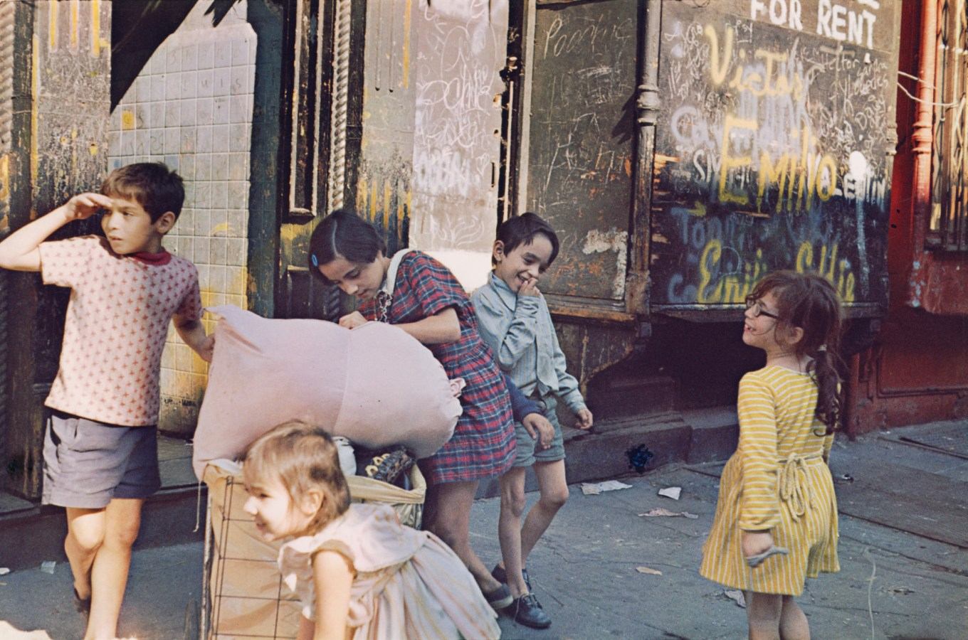 Color photograph of five young children on a city sidewalk before a graffitied storefront