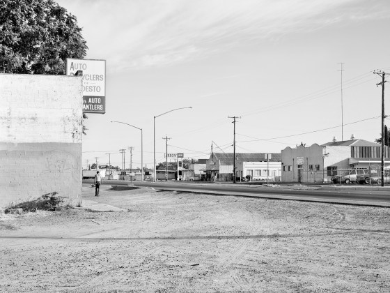 Katy Grannan, Man Walks Alone Through Empty Lot, Intersection of South 9th Street and River Road, Modesto, CA, 2012