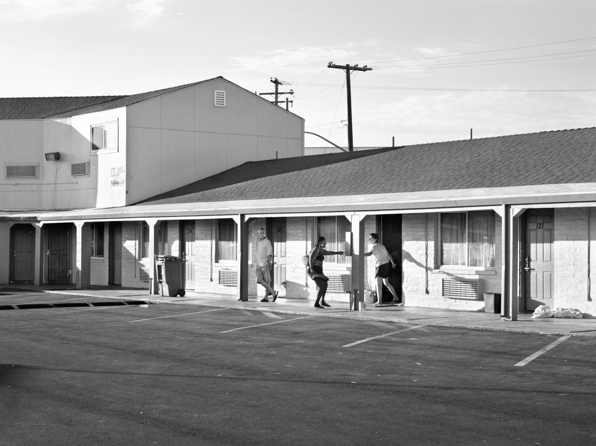 Black-and-white photograph of a a woman pointing at another coming out of a room in a motel parking lot with a man leaning on a pillar