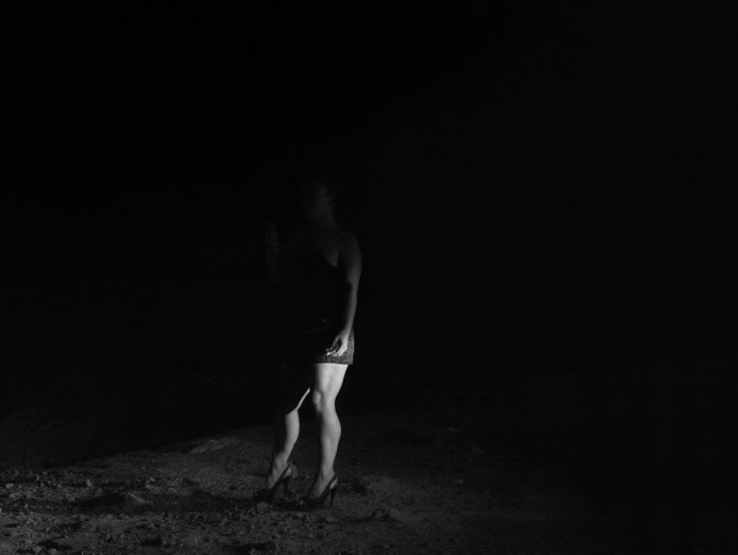 Black-and-white photograph of a woman in high heels standing in the dark with only her legs and arm illuminated