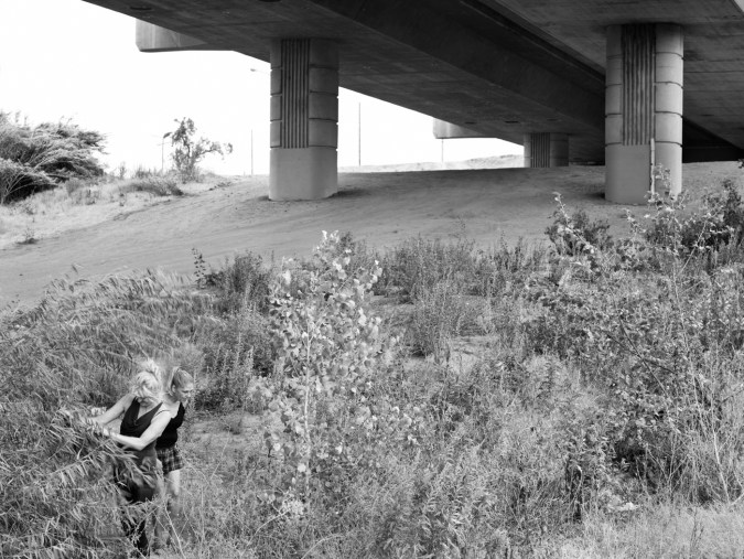 Black-and-white photograph of two women standing in long grass under a concrete bridge