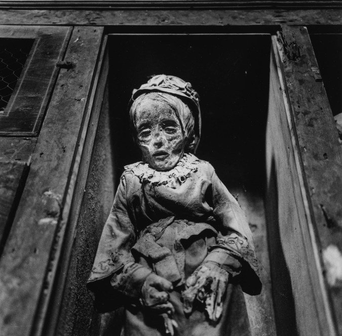 Black-and-white photograph of a preserved child's body propped up in a wooden alcove
