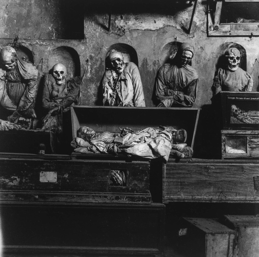 Black-and-white photograph of preserved shrouded bodies standing above wooden boxes containing children's preserved bodies