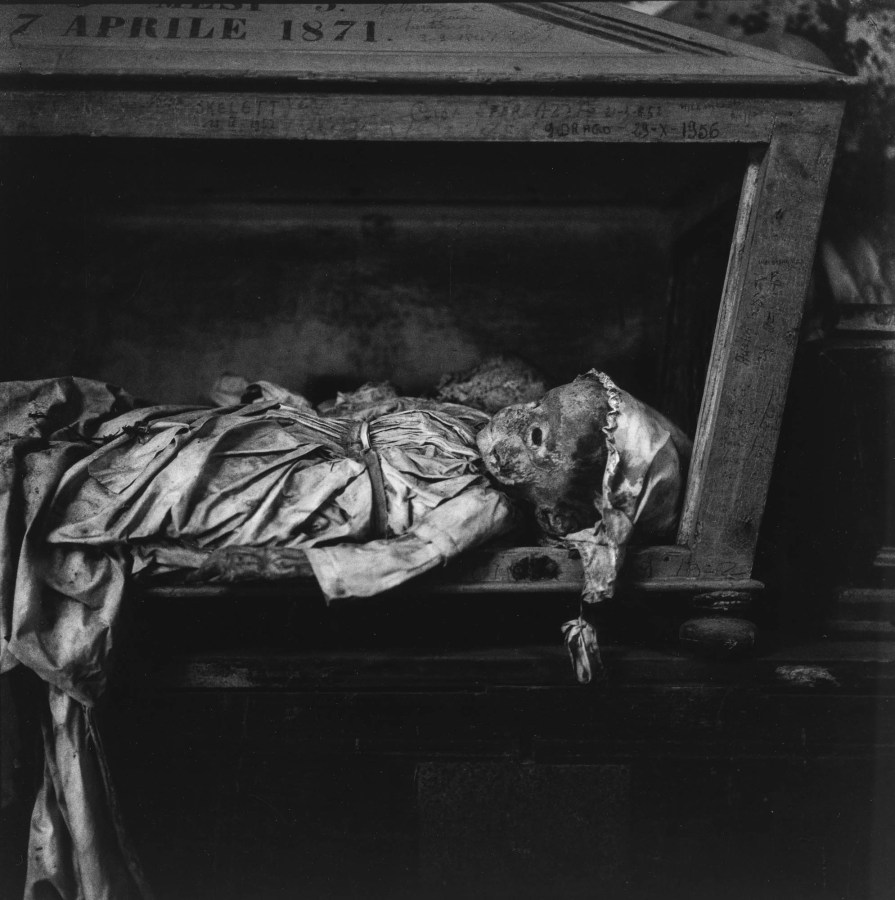 Black-and-white photograph of a preserved child's body lying in a wooden compartment