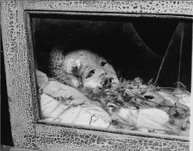 Black-and-white photograph of a preserved child's body lying in a glass-fronted wooden case with dried flowers