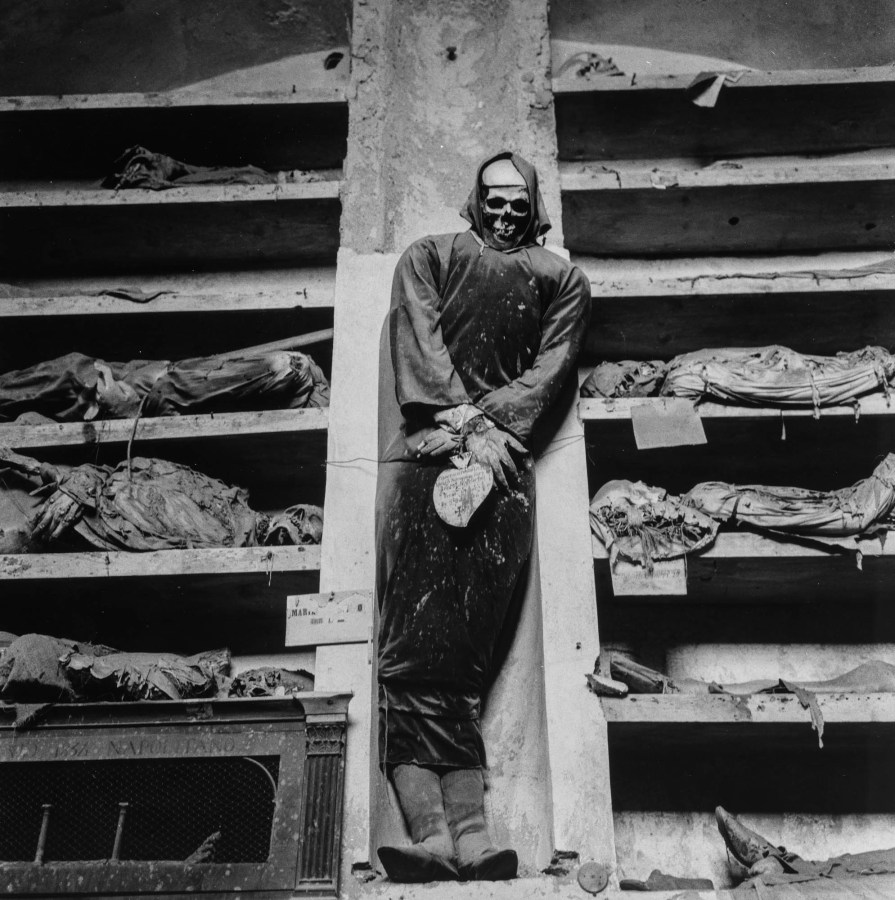 Black-and-white photograph of a hooded preserved body propped up amid other skeletons in compartments