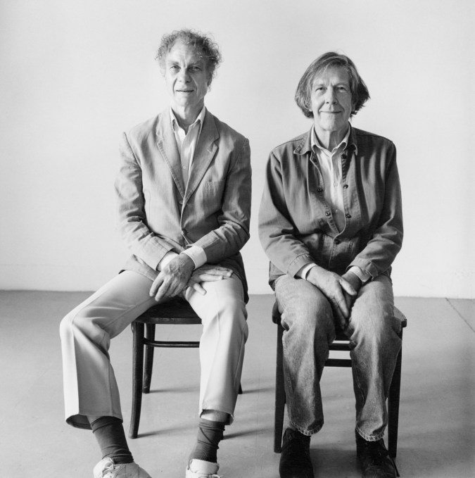 Black-and-white photograph of two older men seated side-by-side with their hands in their laps