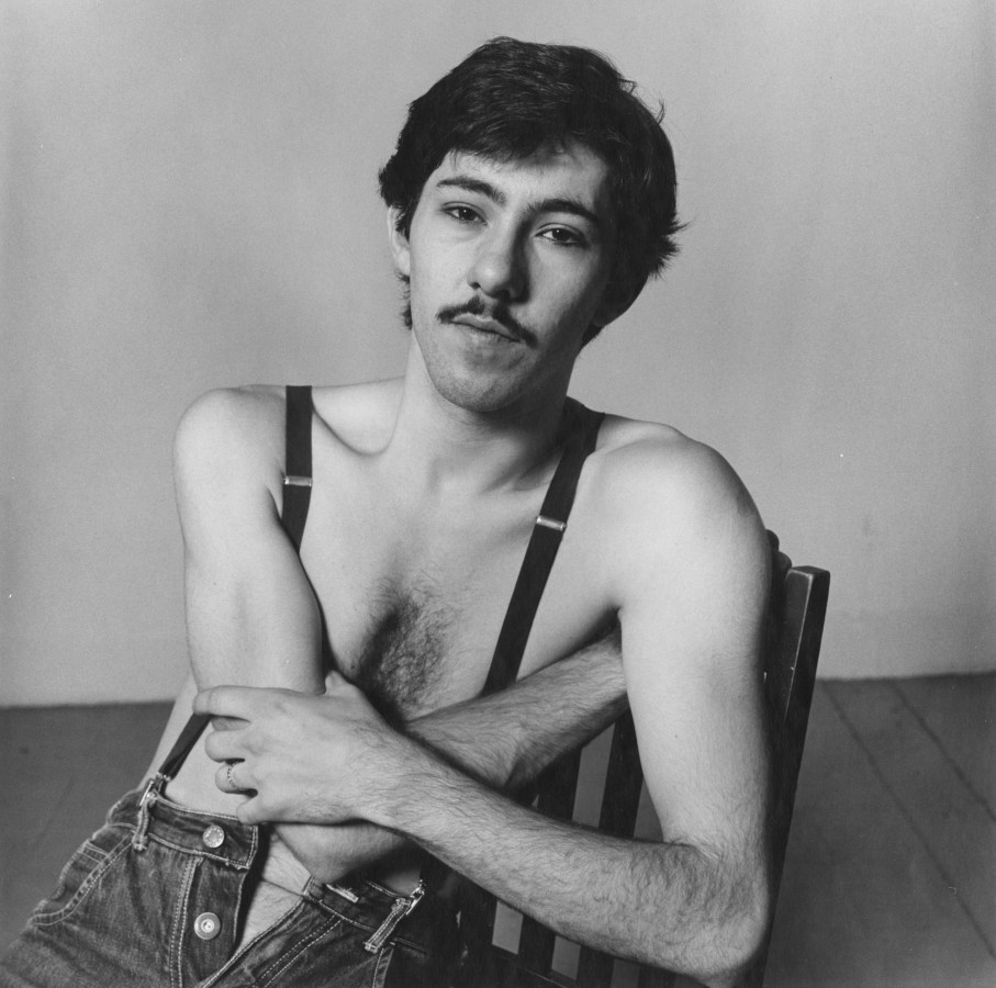 Black-and-white photograph of a seated man with a mustache wearing only suspenders and jeans