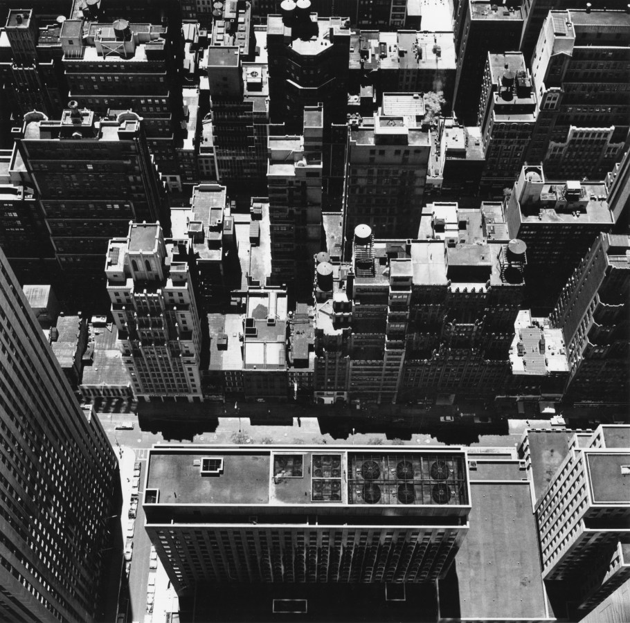 Black-and-white photograph of city buildings and rooftops from a higher vantage point